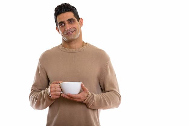 Молодой счастливый мускулистый персидский мужчина улыбается, держа кофе
