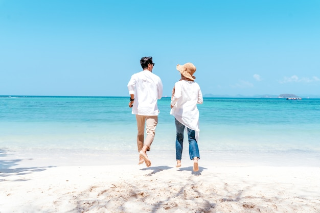 Young happy muslim couple white dress on seashore. travel vacation retirement lifestyle concept. young couple holding hands and turn back on the beach in vacation day. summer time.