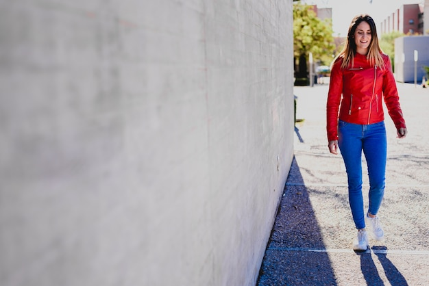 Young happy newly emancipated woman next to a concrete wall, dressed in colorful clothes, looking for her first job.