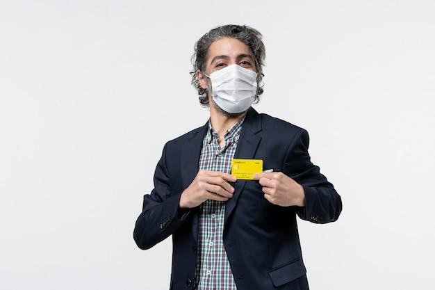 マスクを着用し、孤立した白い背景に彼の銀行カードを保持しているスーツの若い幸せなオフィスアシスタント