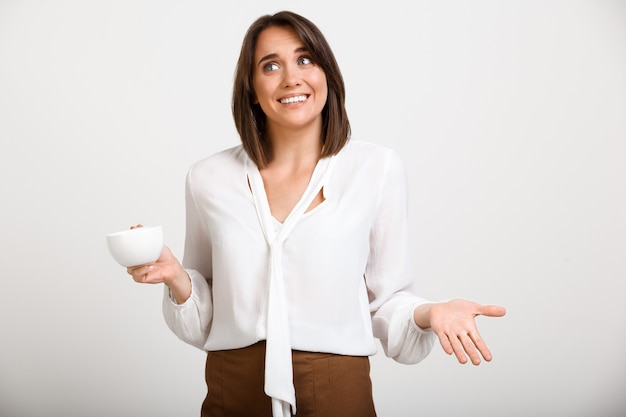 La giovane signora felice dell'ufficio che scrolla le spalle, beve il caffè