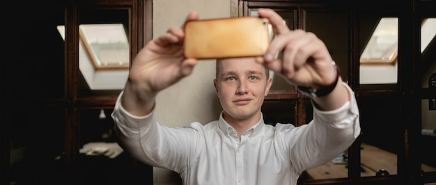 Young happy office worker make selfie at the workplace with smartphone