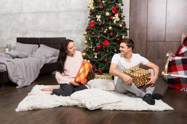 ロフトスタイルの部屋のクリスマスツリーの近くのカーペットに座っている間、パジャマの若い幸せなペアは彼らのプレゼントを喜ぶ