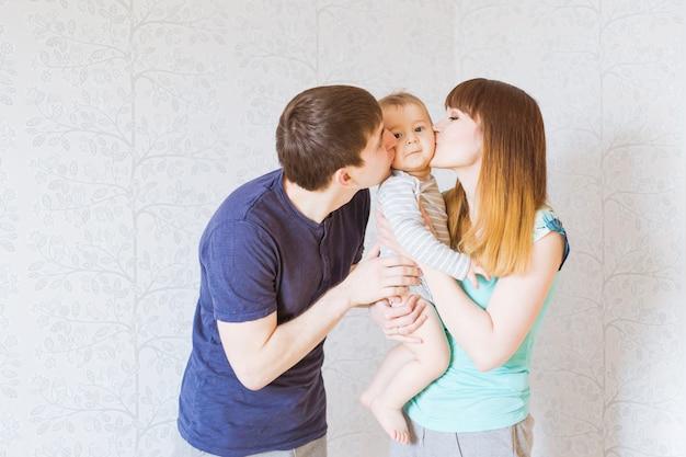 若い幸せな親が男の子、母と父と息子にキス