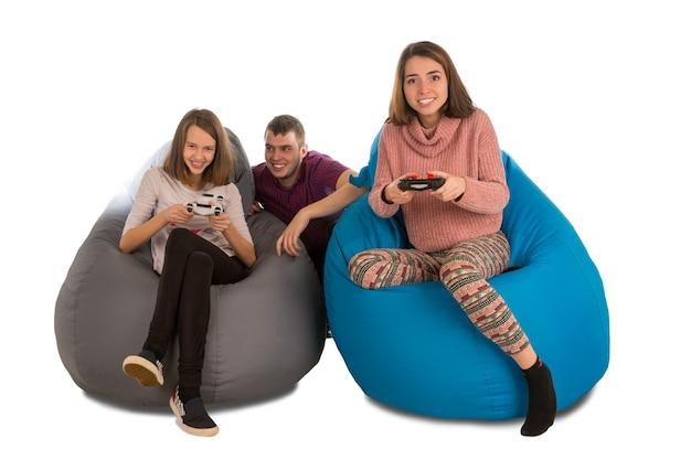 Молодые счастливые люди с энтузиазмом играют в видеоигры, сидя на сине-серых креслах-мешках для гостиной или другой комнаты, изолированной на белом