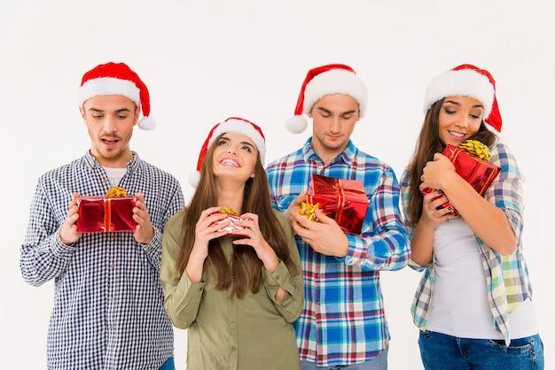 Молодые счастливые люди в шляпах санты с подарками