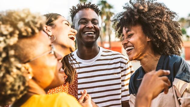 一緒に笑う若い幸せな人々-街の通りで楽しんでいる多民族の友人グループ-外で祝う多様な文化の学生の肖像画-友情、コミュニティ、若者、大学のコンセプト。
