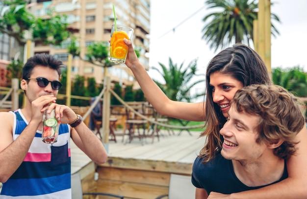 健康的な飲み物を踊り、屋外の夏のパーティーで楽しんでいる若い幸せな人々。若者のライフスタイルのコンセプト。
