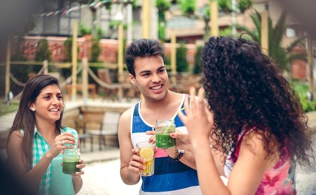 屋外の夏のパーティーで笑っている健康的な飲み物を持つ若い幸せな人々。柵越しに眺める。