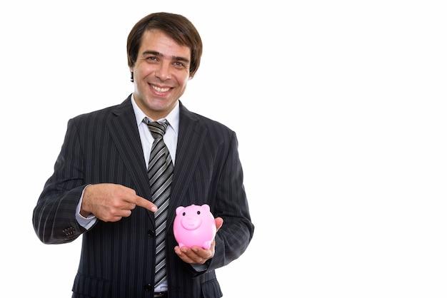 웃 고 돼지 저금통에서 가리키는 젊은 행복 페르시아 사업가
