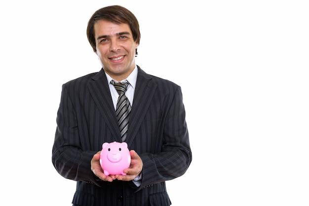 돼지 저금통을 들고 웃 고 젊은 행복 페르시아 사업가