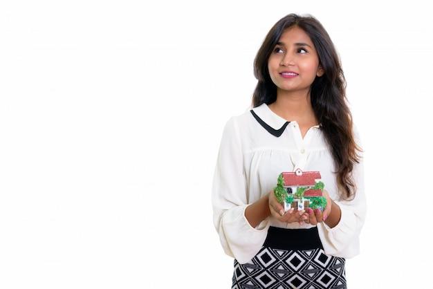 Молодой счастливый персидский бизнесвумен улыбается и думает