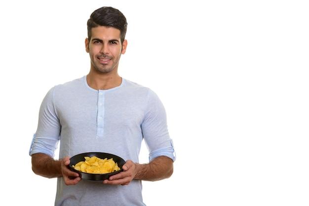 Молодой счастливый персидский мужчина улыбается и держит миску картофельных чипсов