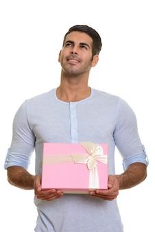 Молодой счастливый персидский мужчина улыбается и держит подарочную коробку, пока думает
