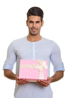 Молодой счастливый персидский мужчина улыбается и держит подарочную коробку