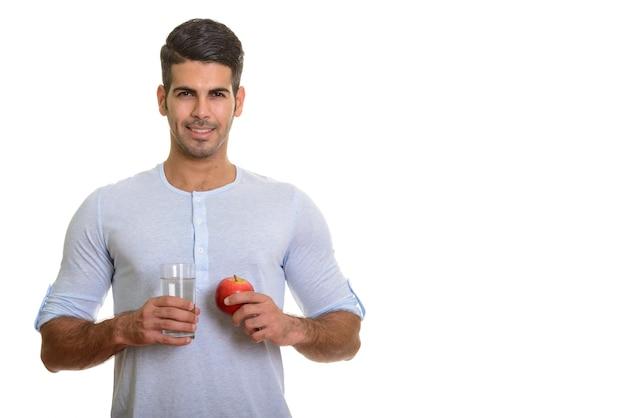 Молодой счастливый персидский мужчина улыбается и держит стакан воды и красное яблоко