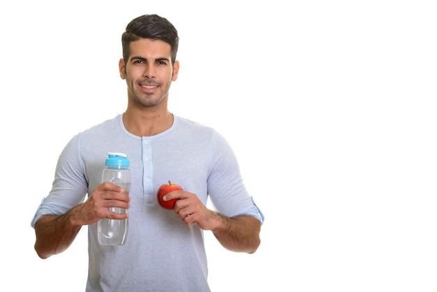 Молодой счастливый персидский мужчина улыбается и держит бутылку с водой и красное яблоко