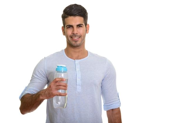 Молодой счастливый персидский мужчина улыбается и держит бутылку с водой