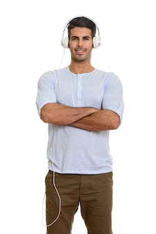 Молодой счастливый персидский мужчина улыбается и слушает музыку с руками