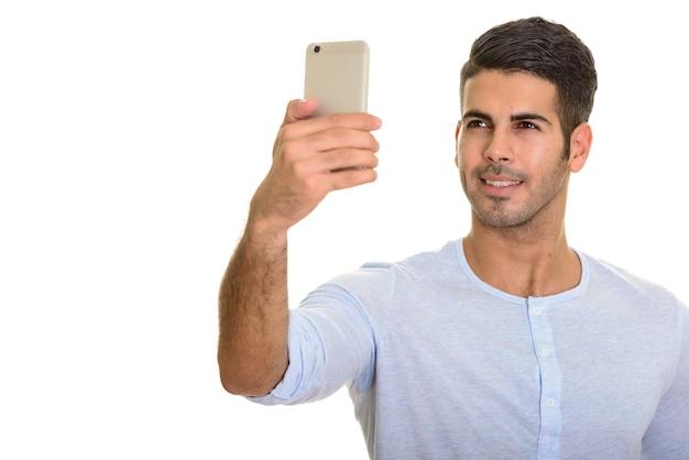 Молодой счастливый персидский мужчина улыбается и делает селфи с мобильным телефоном