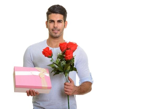 Молодой счастливый персидский мужчина улыбается, держа подарочную коробку и красный r