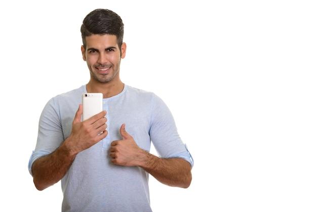 Молодой счастливый персидский человек улыбается, держа мобильный телефон