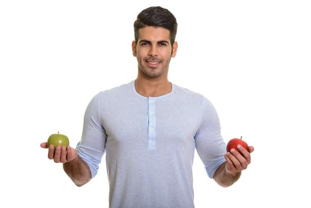 Молодой счастливый персидский мужчина улыбается, держа в руках красное и зеленое яблоко
