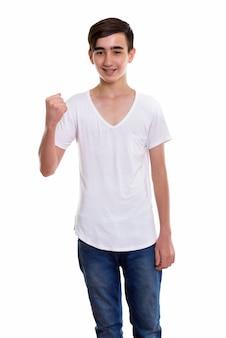 Молодой счастливый персидский подросток улыбается и стоит