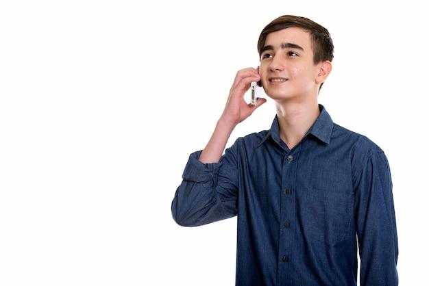 Молодой счастливый персидский мальчик-подросток улыбается и разговаривает по мобильному телефону