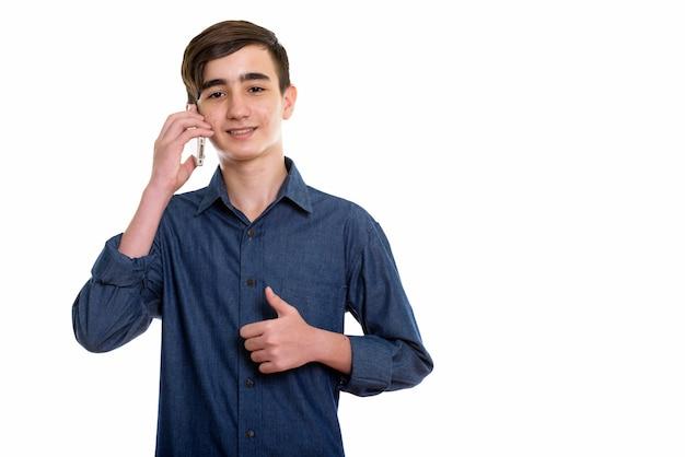 Молодой счастливый персидский мальчик-подросток улыбается во время разговора по мобильному телефону