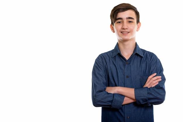 Молодой счастливый персидский мальчик-подросток улыбается со скрещенными руками