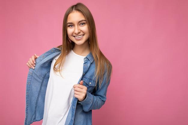 モックアップとデニムシャツのカジュアルな白いtシャツを着てコピースペースで背景の壁に分離された誠実な感情を持つ若い幸せなポジティブ美しいダークブロンドの女性。スマイルコンセプト。