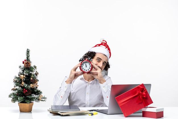 Giovane uomo d'affari positivo felice con il cappello di babbo natale e mostrando l'orologio guardando qualcosa e seduto in ufficio su sfondo bianco