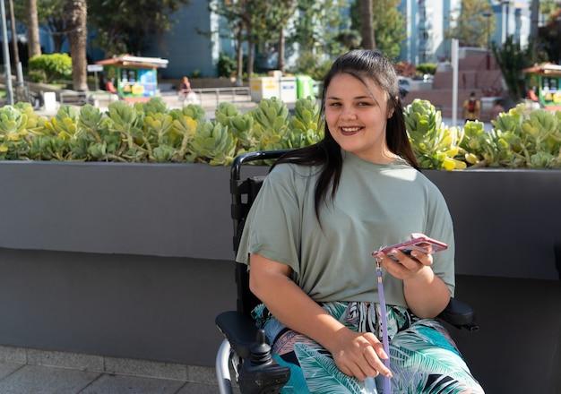 晴れた夏の日に屋外を歩きながらスマートフォンを使用し、カメラに笑みを浮かべて車椅子の若い幸せなポジティブ障害者女性