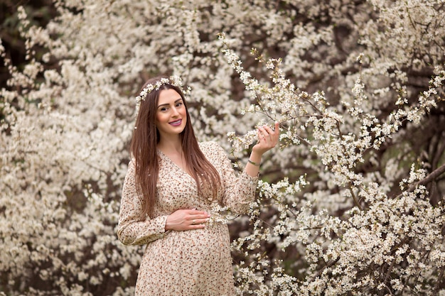 Young happy pregnant girl on a background of flowering trees.