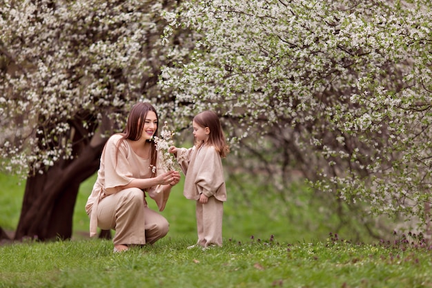 Young happy pregnant girl with a daughter on a background of flowering trees.
