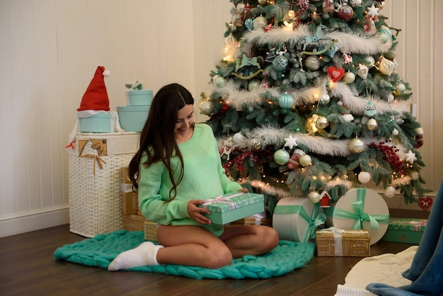 Young happy pregnant woman siting near new year tree and opening a gift.