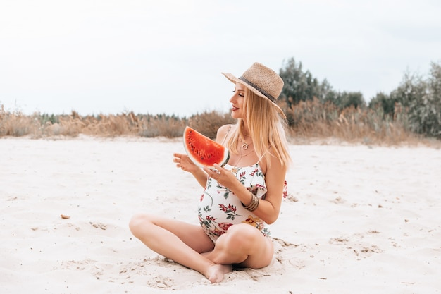 Young happy pregnant woman in a swimsuit and hat with watermelon