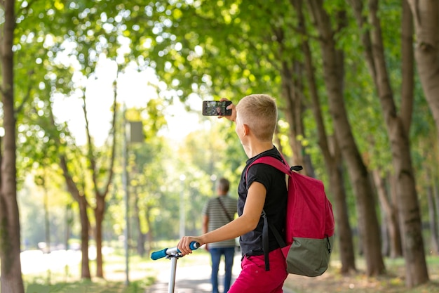 공원에서 따뜻하고 화창한 여름 날에 스쿠터를 타고 스쿠터를 타고있는 동안 smartpone에서 셀카를 복용하는 젊은 행복 초반 이었죠 소년