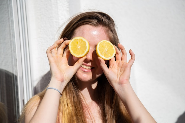 Young happy pretty female in casual summer dress sitting on terrace and covering eyes with ripe lemons