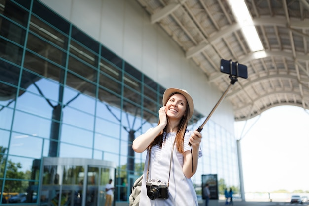 Young happy pretty traveler tourist woman with retro vintage photo camera doing selfie on mobile phone with monopod selfish stick at airport