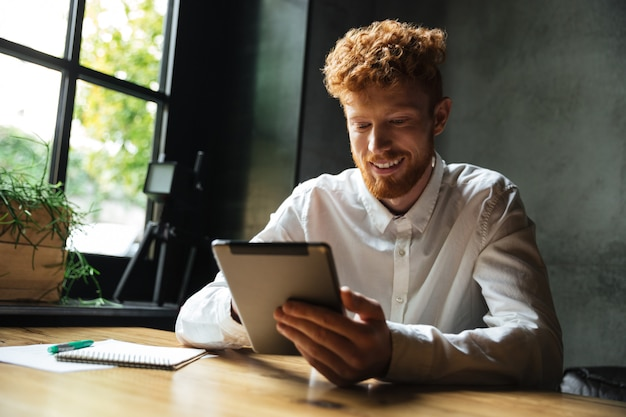 Young happy readhead bearded man using tablet, looking at screen