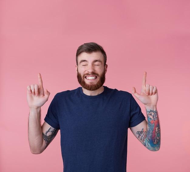 若い幸せな赤ひげを生やした若い男は、まばたきと幸運を願って、ピンクの背景で隔離されたスペースをコピーするために指を指しています。