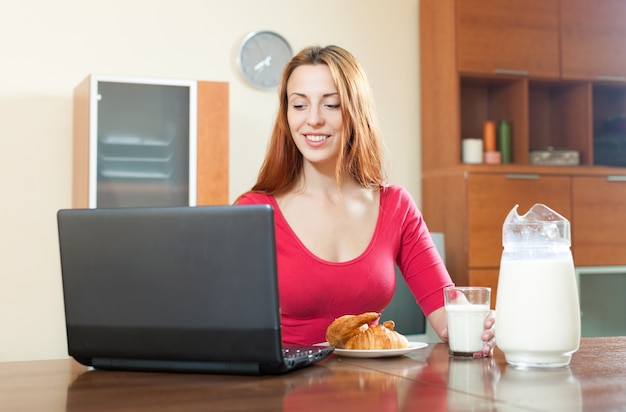 Young happy red-haired girl in pink using laptop during breakfast at home