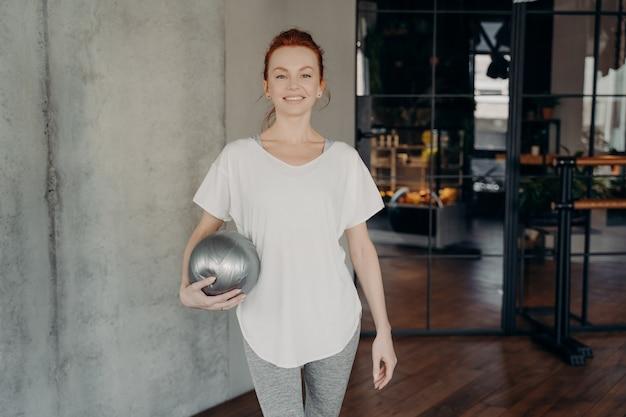 은색 핏볼을 들고 흰색 티셔츠와 회색 레깅스를 입고 미소로 카메라를 쳐다보며 피트니스 스튜디오에 서 있는 젊은 행복한 빨간 머리 낚시를 좋아하는 여성. 사람과 스포츠 개념