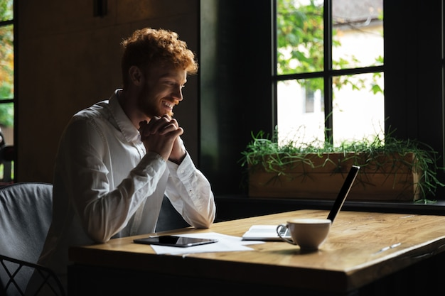 Young happy redhead bearded man holding hands together sitting in the cafe, looking at laptop screen