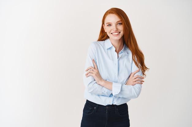 앞에서 웃고 있는 젊은 행복한 빨간 머리 여성, 자신감 있는 가슴에 팔짱을 끼고 흰 벽 위에 사무실 블라우스를 입고 서 있는