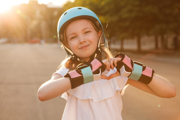 Young happy rollerblader girl wearing helmet, showing heart sign with her hands