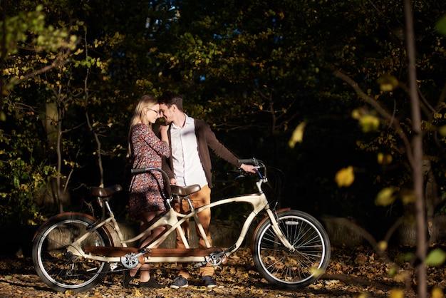 Молодые счастливые романтичные пары, бородатый мужчина и привлекательная модная женщина близко друг к другу на двойном велосипеде на открытом воздухе в осеннем парке или лесу