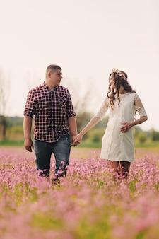 夏の日に花のフィールドを歩いて若い幸せなロマンチックな妊娠中のカップル。妊娠中の女性が赤ちゃんを期待しています。将来のママとパパ、家族。母の日、父の日。コピースペース。